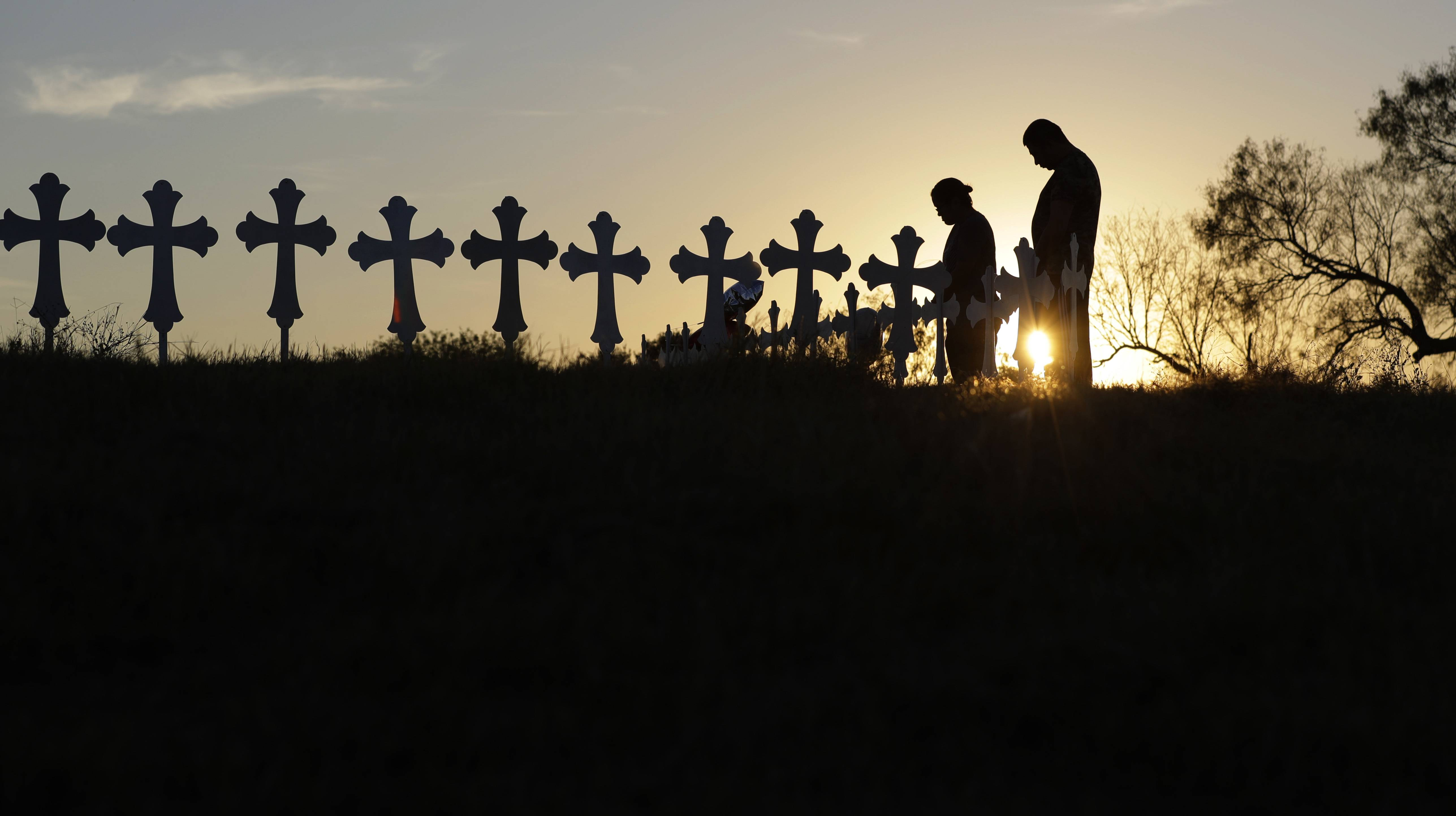 Kenneth and Irene Hernandez pay their respects Monday as they visit a makeshift memorial with crosses placed near the scene of a shooting at the First Baptist Church of Sutherland Springs in Sutherland Springs, Texas. A man opened fire inside the church in the small South Texas community on Sunday, killing and wounding many.