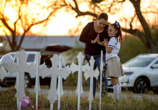 Meredith Cooper, of San Antonio, Texas, and her 8-year-old daughter, Heather, visit a memorial of 26 metal crosses near First Baptist Church in Sutherland Springs, Texas, Monday Nov. 6, 2017. The gunman of a deadly shooting at the small-town Texas church had a history of domestic violence and sent threatening text messages to his mother-in-law, a member of First Baptist, before the attack, authorities said Monday. (Jay Janner/Austin American-Statesman via AP)