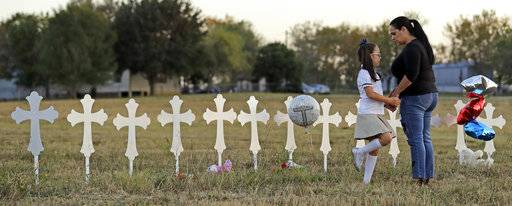 Meredith Cooper, right, and her daughter Heather, 8, visit a line of crosses before a vigil for the victims of the First Baptist Church shooting, Monday, Nov. 6, 2017, in Sutherland Springs, Texas. A man opened fire inside the church in the small South Texas community on Sunday, killing more than 20 and injuring others.
