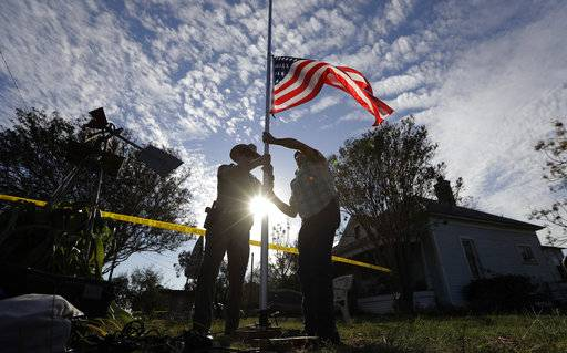 A law enforcement officer helps a man changes a flag to half-staff near the scene of a shooting at the First Baptist Church of Sutherland Springs to honor victims, Monday, Nov. 6, 2017, in Sutherland Springs, Texas. A man opened fire inside the church in the small South Texas community on Sunday, killing and wounding many.