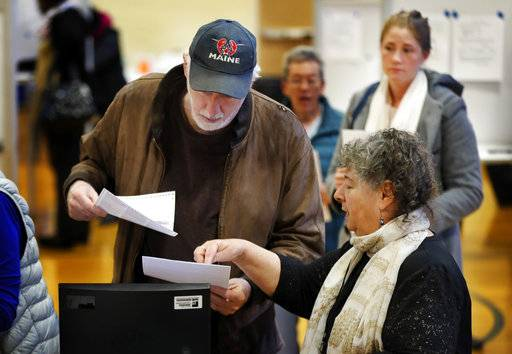 Michael Parent, left, gets instructions on submitting his ballots from warden Denise Shames while voting Tuesday, Nov. 7, 2017, in Portland, Maine. Voters in Maine will decide if they want to join 31 other states and expand Medicaid under former President Barack Obama's Affordable Care Act. It's the first time since the law took effect that the expansion question has been put before voters.