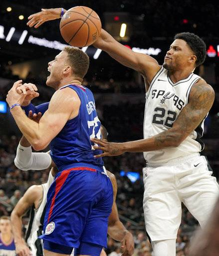 San Antonio Spurs forward Rudy Gay (22) swats the ball away from Los Angeles Clippers' Blake Griffin during the first half of an NBA basketball game, Tuesday, Nov. 7, 2017, in San Antonio. (AP Photo/Darren Abate)
