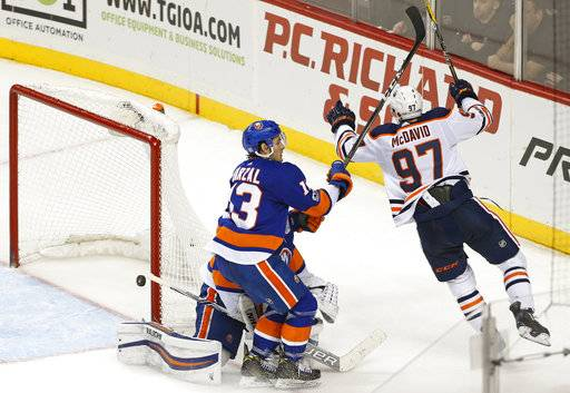 Edmonton Oilers center Connor McDavid (97) celebrates after scoring the winning goal in overtime of an NHL hockey game against the New York Islanders in New York, Tuesday, Nov. 7, 2017. Islanders center Mathew Barzal (13) and Islanders goalie Thomas Greiss, of Germany, (partially obscured) react to the game-winning score. (AP Photo/Kathy Willens)