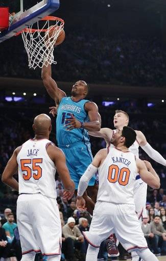 Charlotte Hornets' Dwight Howard (12) drives past New York Knicks' Jarrett Jack (55), Enes Kanter (00) and Kristaps Porzingis during the first half of an NBA basketball game Tuesday, Nov. 7, 2017, in New York.
