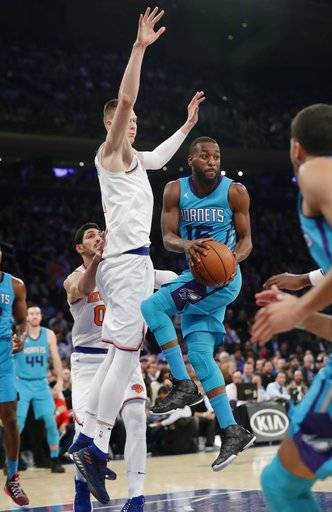 Charlotte Hornets' Kemba Walker (15) passes the ball away from New York Knicks' Kristaps Porzingis during the first half of an NBA basketball game Tuesday, Nov. 7, 2017, in New York.
