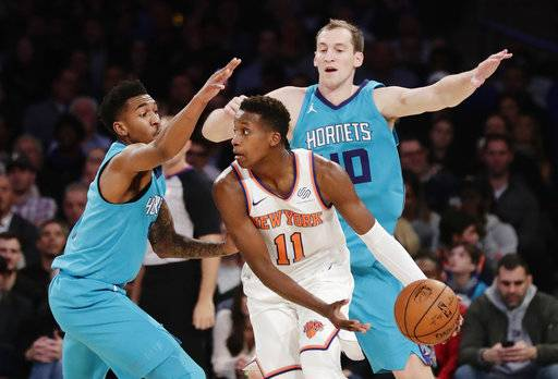 New York Knicks' Frank Ntilikina (11) is defended by Charlotte Hornets' Cody Zeller, right, and Malik Monk during the first half of an NBA basketball game Tuesday, Nov. 7, 2017, in New York.