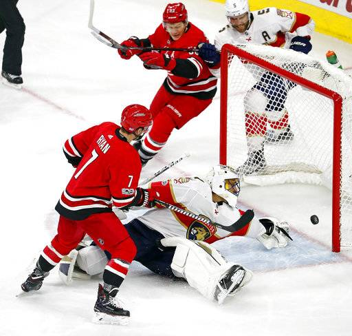 Carolina Hurricanes' Derek Ryan (7) tips the puck past Florida Panthers goalie Roberto Luongo (1) for the game winning goal as Hurricanes' Jeff Skinner (53) and Panthers' Aaron Ekblad (5) look on, during the third period of an NHL hockey game, Tuesday, Nov. 7, 2017, in Raleigh, N.C.
