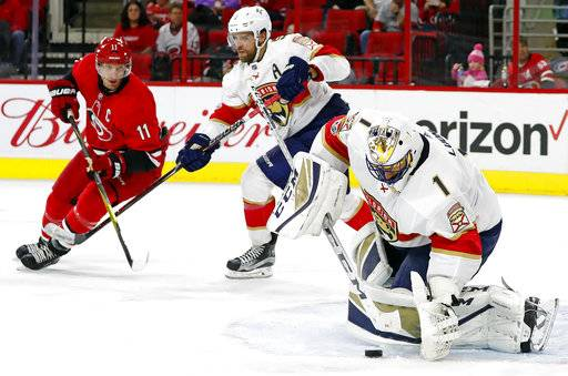 Florida Panthers goalie Roberto Luongo (1) freezes the puck as teammate Aaron Ekblad (5) holds off Carolina Hurricanes' Jordan Staal (11) during the second period of an NHL hockey game, Tuesday, Nov. 7, 2017, in Raleigh, N.C.