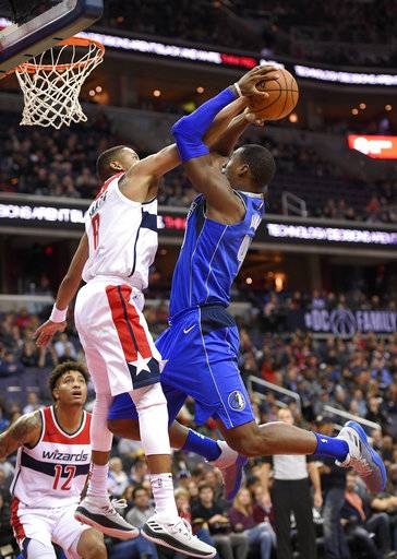 Washington Wizards guard Tim Frazier, left, fouls Dallas Mavericks forward Harrison Barnes, right, during the first half of an NBA basketball game, Tuesday, Nov. 7, 2017, in Washington. Also seen is Wizards forward Kelly Oubre Jr. (12).