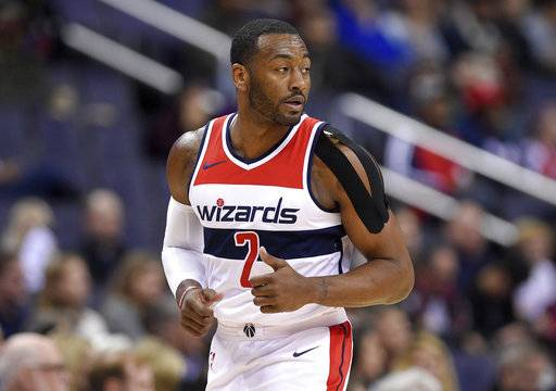 Washington Wizards guard John Wall (2) runs down the court with a heavily taped shoulder during the first half of an NBA basketball game against the Dallas Mavericks, Tuesday, Nov. 7, 2017, in Washington.