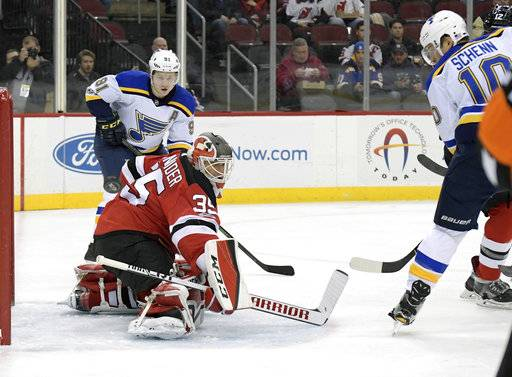 New Jersey Devils goalie Cory Schneider (35) deflects the puck as St. Louis Blues center Brayden Schenn (10) and right wing Vladimir Tarasenko (91) watch during the first period of an NHL hockey game Tuesday, Nov. 7, 2017, in Newark, N.J. (AP Photo/Bill Kostroun