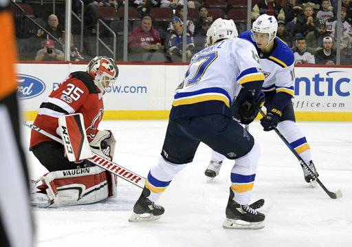 New Jersey Devils goalie Cory Schneider (35) deflects the puck as St. Louis Blues left wing Jaden Schwartz (17) and center Brayden Schenn (10) look for a rebound during the first period of an NHL hockey game Tuesday, Nov. 7, 2017, in Newark, N.J. (AP Photo/Bill Kostroun