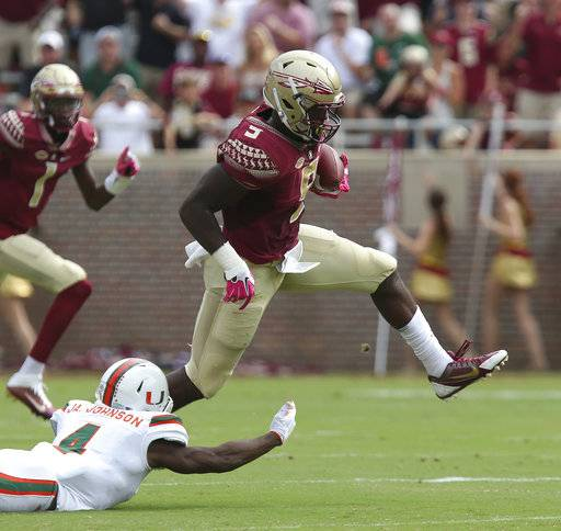 FILE - In this Oct. 7, 2017, file photo, Florida State's Jacques Patrick eludes Miami's Jaquan Johnson to gain yardage in the first quarter of an NCAA college football game,in Tallahassee, Fla. Florida State's offense has been decimated by injuries, but the Seminoles are getting a rare bit of good news. Running back Jacques Patrick was feared lost for the season after an injury on Oct. 21 against Louisville but indications are he could be back when the Seminoles travel to No. 3 Clemson on Saturday. (AP Photo/Steve Cannon, File)