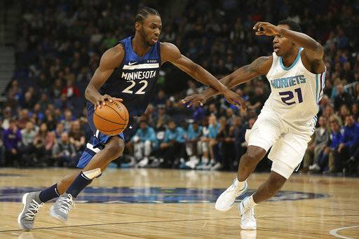 Minnesota Timberwolves forward Andrew Wiggins (22) drives the ball around Charlotte Hornets guard Treveon Graham (21) in the first half of an NBA basketball game Sunday, Nov. 5, 2017, in Minneapolis.