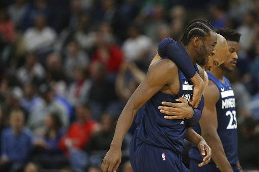 Minnesota Timberwolves forward Taj Gibson wraps his arms around teammate Andrew Wiggins after Wiggins scored a basket against the Charlotte Hornets in the second half of an NBA basketball game Sunday, Nov. 5, 2017, in Minneapolis. The Wolves won 112-94.