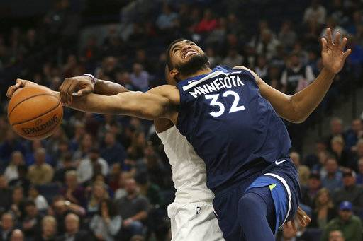 Minnesota Timberwolves center Karl-Anthony Towns (32) gets tangled up with Charlotte Hornets center Dwight Howard, left, in the first half of an NBA basketball game, Sunday, Nov. 5, 2017, in Minneapolis.