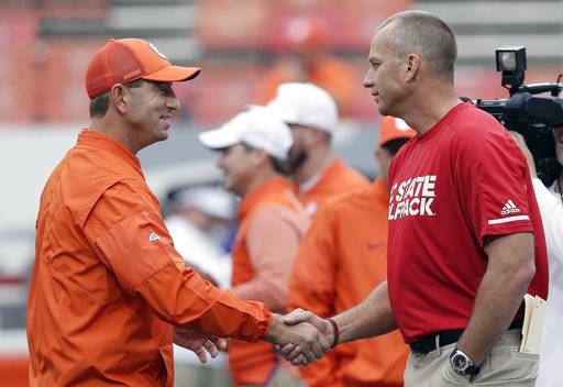 Clemson head coach Dabo Swinney and North Carolina State head coach Dave Doeren shake hands prior to an NCAA college football game in Raleigh, N.C., Saturday, Nov. 4, 2017.