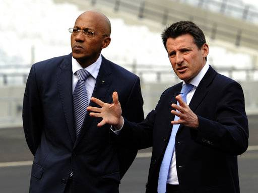 FILE- In this Tuesday, March 29, 2011 file photo,  former Namibian athlete and Chairman of the IOC Athletes' Commission Frank Fredericks, left, listens to former British athlete and head of the LOCOG, Sebastian Coe, right, after laying the final bit of turf in the London 2012 Olympic stadium, London. The International Olympic Committee has suspended Frank Fredericks, Tuesday, Nov. 7, 2017. The decision comes four days after he was charged in a French investigation of suspected bribery in the 2016 Olympic host city vote.