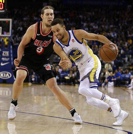 Golden State Warriors' Stephen Curry, right, drives the ball against Miami Heat forward Kelly Olynyk (9) during the second half of an NBA basketball game Monday, Nov. 6, 2017, in Oakland, Calif. Warriors won, 97-80. (AP Photo/Ben Margot)