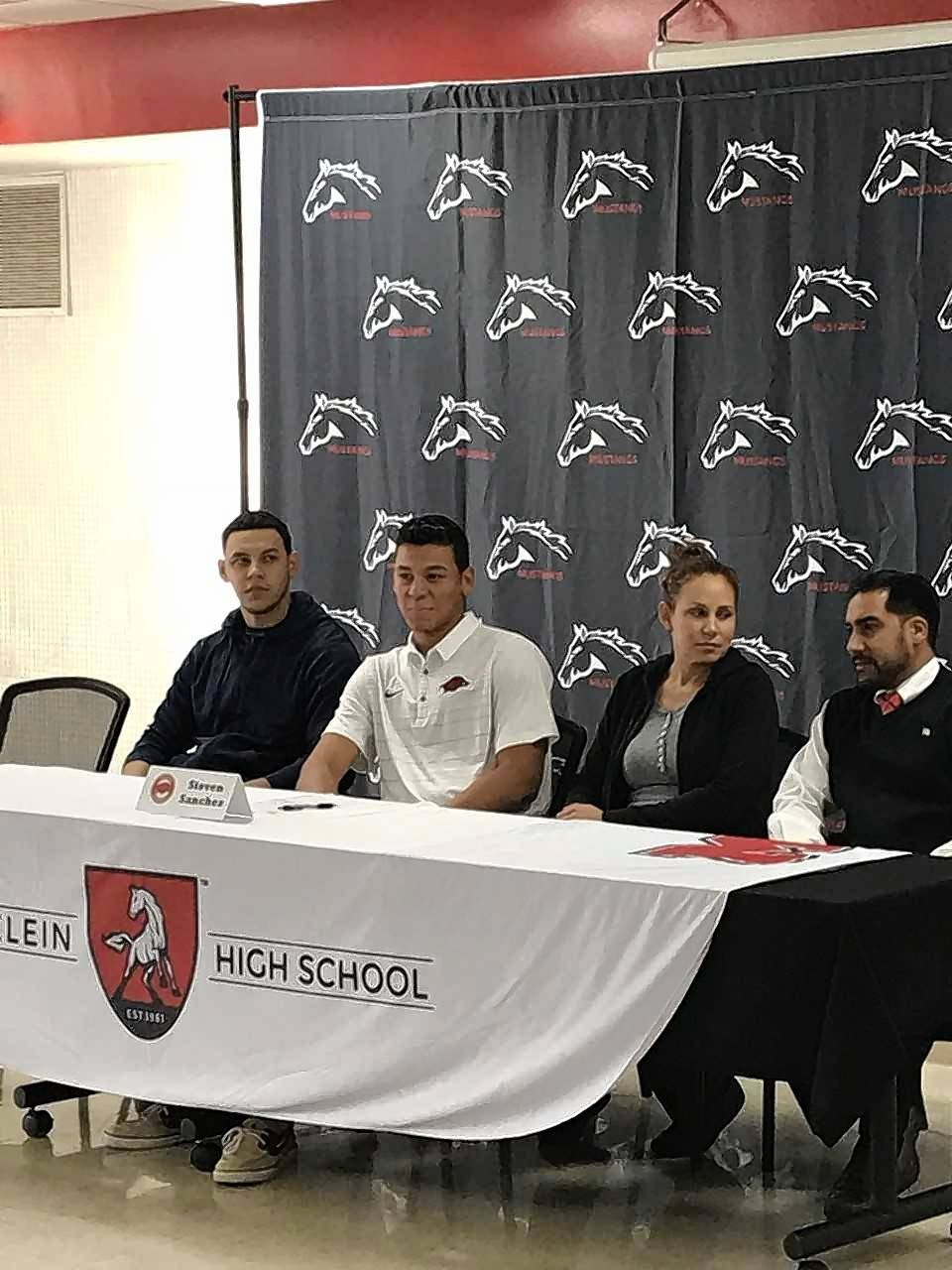 Joined by family members, Mundelein's Steven Sanchez makes his college baseball choice official during a letter of intent signing ceremony Wednesday. He will pitch next school year at Arkansas.