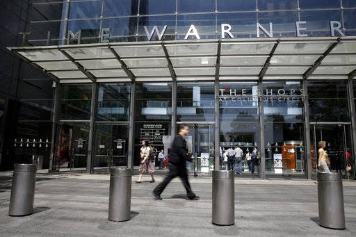 "FILE - In this Tuesday, May 26, 2015, file photo, pedestrians walk by an entrance to the Time Warner Center in New York. AT&T now says it's ""uncertain� when its $85 billion Time Warner purchase will close. AT&T had maintained that the deal would be done by the end of 2017."