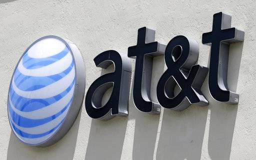 "FILE - This Thursday, July 27, 2017, file photo shows an AT&T logo at a store in Hialeah, Fla. AT&T now says it's ""uncertain� when its $85 billion Time Warner purchase will close. AT&T had maintained that the deal would be done by the end of 2017."