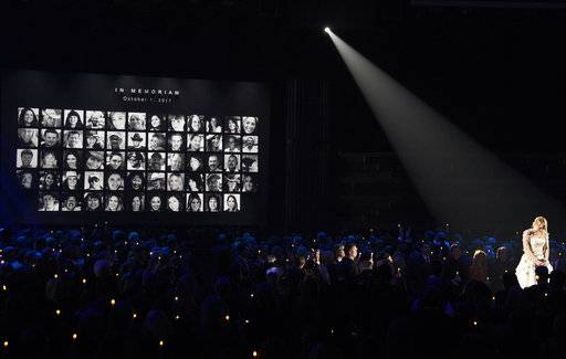 "Carrie Underwood pauses during an emotional performance of ""Softly and Tenderly"" during an In Memoriam tribute at the 51st annual CMA Awards at the Bridgestone Arena on Wednesday, Nov. 8, 2017, in Nashville, Tenn. Pictured on screen are victims of the Route 91 Harvest mass shooting. (Photo by Chris Pizzello/Invision/AP)"