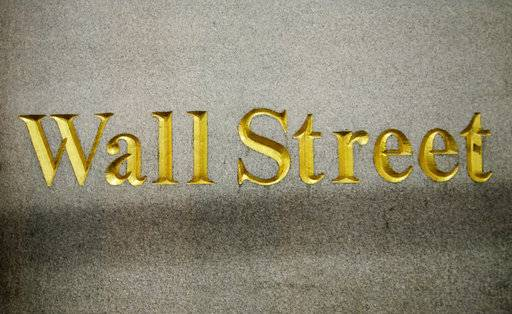 FILE - In this Oct. 8, 2014, file photo, a Wall Street address is carved in the side of a building in New York. U.S. stocks are lower in early trading Wednesday, Nov. 8, 2017, as falling interest rates continue to put pressure on banks, and technology and energy companies also move lower.