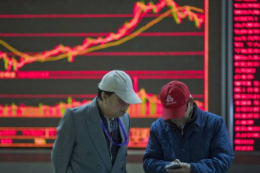 Men chat at a stock brokerage in Beijing, China, Wednesday, Nov. 8, 2017. Asian stocks were mixed Wednesday after Wall Street declined as President Donald Trump delivered a new warning to North Korea in a speech to South Korean lawmakers.
