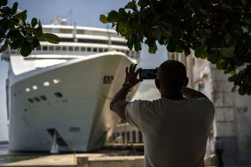 FILE - In this June 17, 2017, file photo, a man takes a photo of a cruise ship in Havana harbor, Cuba. President Donald Trump announced a new policy in June that partially rolled back the recent diplomatic opening with Cuba. New regulations implementing that policy are being unveiled Wednesday.