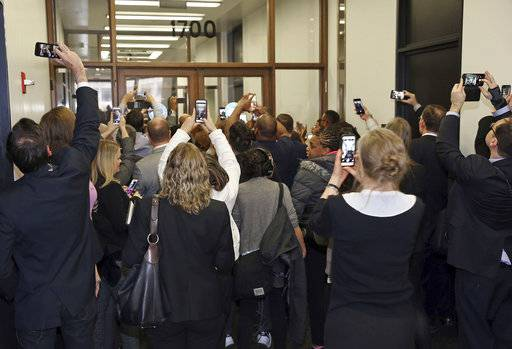 People rush the doors of the jury assembly room as former President Barack Obama arrives for jury duty in the Daley Center on Wednesday, Nov. 8, 2017, in Chicago. Obama is in line to be paid the same $17.20 a day that others receive for reporting for jury duty. (Kevin Tanaka/Sun Times via AP)