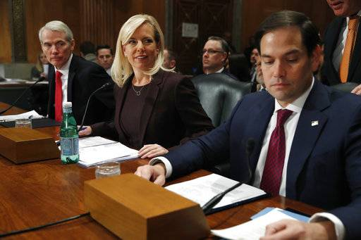 Sen. Rob Portman, R-Ohio, left, and Sen. Marco Rubio, R-Fla., right, take their seats to speak on behalf of Kirstjen Nielsen, center, at a Senate Homeland Security and Governmental Affairs committee hearing on Nielsen's nomination to be Department of Homeland Security Secretary, Wednesday, Nov. 8, 2017, on Capitol Hill in Washington.