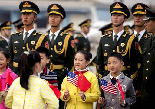 Chinese soldiers and children holding U.S. and Chinese flags line up on the tarmac to greet President Donald Trump as he arrives at Beijing Airport, Wednesday, Nov. 8, 2017, in Beijing, China. Trump is on a five country trip through Asia traveling to Japan, South Korea, China, Vietnam and the Philippines.