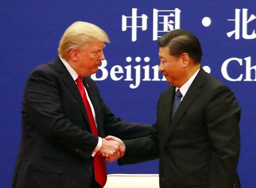 U.S. President Donald Trump, left, and Chinese President Xi Jinping shake hands during a business event at the Great Hall of the People in Beijing, Thursday, Nov. 9, 2017.