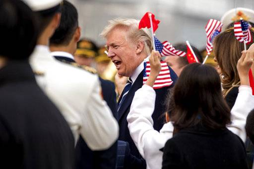 Children wave U.S. and Chinese flags as President Donald Trump arrives at Beijing Airport, Wednesday, Nov. 8, 2017, in Beijing, China. Trump is on a five country trip through Asia traveling to Japan, South Korea, China, Vietnam and the Philippines.