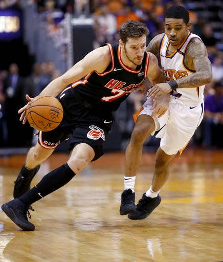 Miami Heat guard Goran Dragic (7) drives around Phoenix Suns guard Tyler Ulis during the first half of an NBA basketball game, Wednesday, Nov. 8, 2017, in Phoenix.