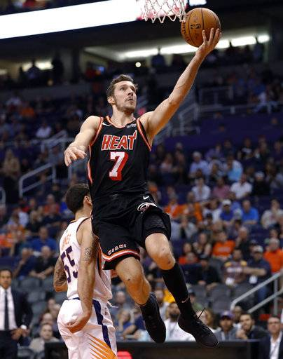 Miami Heat guard Goran Dragic (7) scores over Phoenix Suns guard Mike James (55) during the first half of an NBA basketball game, Wednesday, Nov. 8, 2017, in Phoenix.