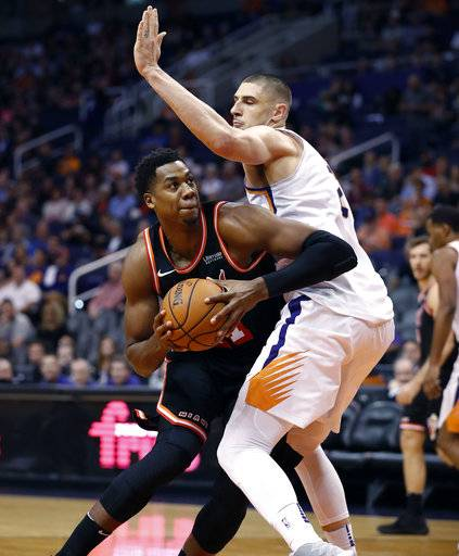 Miami Heat center Hassan Whiteside goes around Phoenix Suns center Alex Len, right, during the first half of an NBA basketball game, Wednesday, Nov. 8, 2017, in Phoenix.