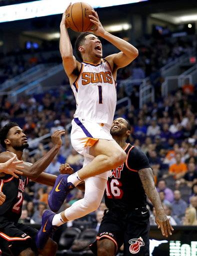 Phoenix Suns guard Devin Booker (1) shoots between Miami Heat forward James Johnson (16) and guard Wayne Ellington (2) during the second half of an NBA basketball game, Wednesday, Nov. 8, 2017, in Phoenix.