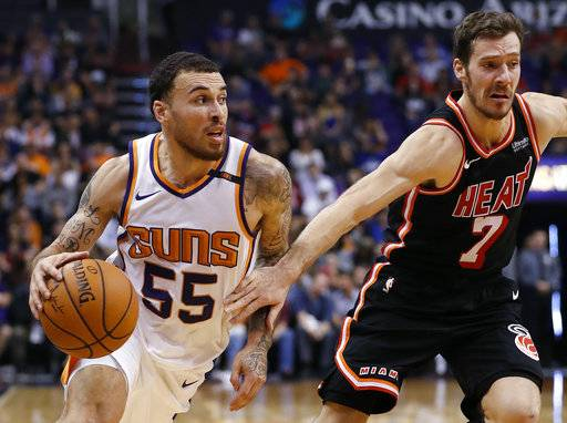 Phoenix Suns guard Mike James (55) slips past Miami Heat guard Goran Dragic (7) during the second half of an NBA basketball game, Wednesday, Nov. 8, 2017, in Phoenix.
