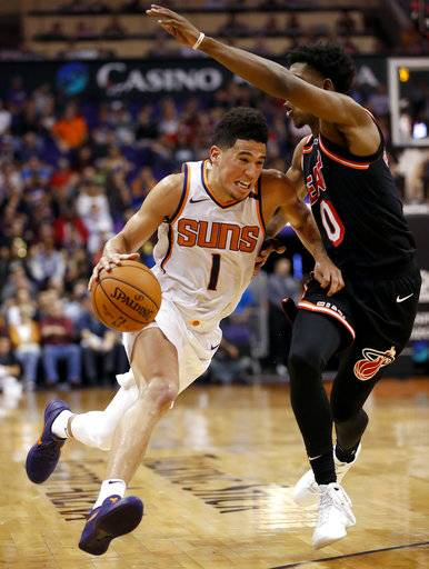Phoenix Suns guard Devin Booker (1) drives around Miami Heat forward Josh Richardson during the second half of an NBA basketball game, Wednesday, Nov. 8, 2017, in Phoenix.