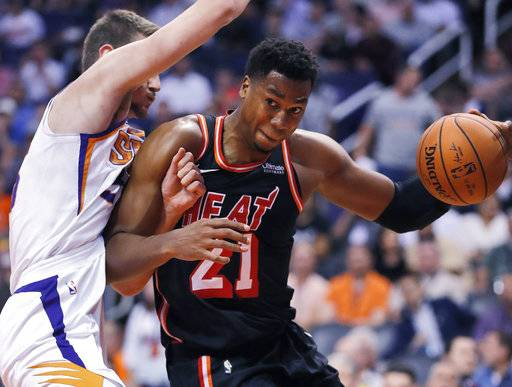 Miami Heat center Hassan Whiteside (21) drives around Phoenix Suns forward Dragan Bender during the first half of an NBA basketball game, Wednesday, Nov. 8, 2017, in Phoenix.