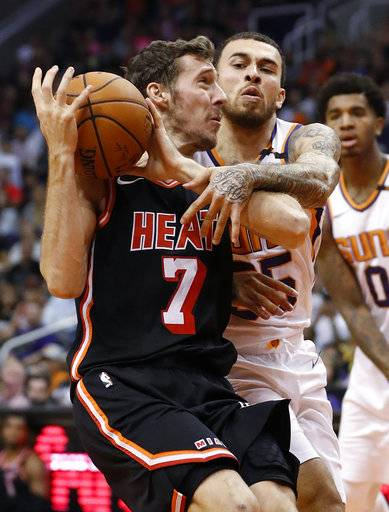 Miami Heat guard Goran Dragic (7) is fouled by Phoenix Suns guard Mike James during the first half of an NBA basketball game, Wednesday, Nov. 8, 2017, in Phoenix.
