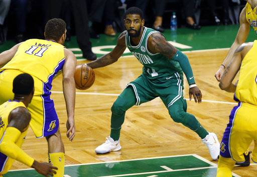 Boston Celtics' Kyrie Irving looks for an opening past Los Angeles Lakers' Brook Lopez and other defenders during the first quarter of an NBA basketball game in Boston Wednesday, Nov. 8, 2017.