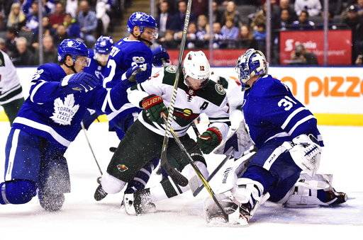 Toronto Maple Leafs defenseman Ron Hainsey, left, hits Minnesota Wild center Eric Staal (12) into goalie Frederik Andersen (31) during the third period of an NHL hockey game Wednesday, Nov. 8, 2017, in Toronto. (Frank Gunn/The Canadian Press via AP)
