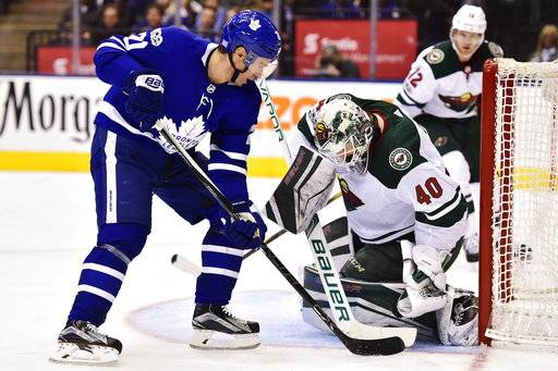 Minnesota Wild goalie Devan Dubnyk (40) makes a save on Toronto Maple Leafs center Dominic Moore (20) during the second period of an NHL hockey game Wednesday, Nov. 8, 2017, in Toronto. (Frank Gunn/The Canadian Press via AP)