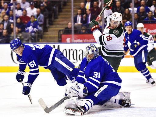 Toronto Maple Leafs goalie Frederik Andersen (31) and defenseman Jake Gardiner (51) and Minnesota Wild center Luke Kunin (19) watch as the puck goes wide of the net during the first period of an NHL hockey game Wednesday, Nov. 8, 2017, in Toronto. (Frank Gunn/The Canadian Press via AP)