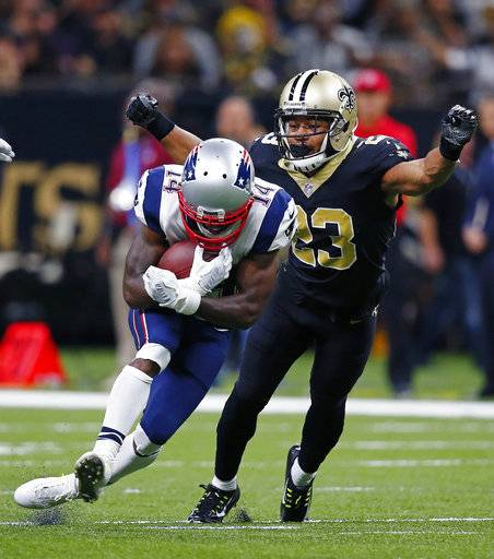 FILE - In this Sept. 17, 2017, file photo, New Orleans Saints cornerback Marshon Lattimore (23) tries to tackle New England Patriots wide receiver Brandin Cooks (14) during the second half of an NFL football game in New Orleans.