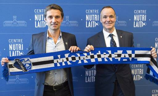 Remi Garde, left, the new head coach of the Montreal Impact, and team president Joey Saputo pose with a scarf during an MLS soccer news conference in Montreal, Wednesday, Nov. 8, 2017. (Paul Chiasson/The Canadian Press via AP)