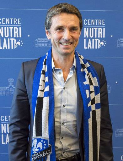 Remi Garde, the new head coach of the Montreal Impact, poses with a scarf during an MLS soccer news conference in Montreal, Wednesday, Nov. 8, 2017. (Paul Chiasson/The Canadian Press via AP)